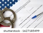 Small photo of District court warrant for the arrest of a witness in a civil action papers with handcuffs and blue pen on United States flag. Permission to witness arrest