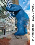 """Small photo of Denver, USA - December 25, 2019: The 40-foot-high Blue Bear """"I see what you mean"""" sculpture imparts a sense of fun and playfulness as it peers into Denver's downtown convention center."""