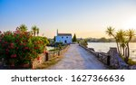 Ypapanti Church - Beautiful scenery at sunset in Gouvia Bay – small ancient white church on a pier, Corfu island, Ionian sea, Greece, Europe