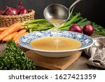 Small photo of Pouring chicken bone broth from a ladle into a vintage plate, with fresh vegetables in the background