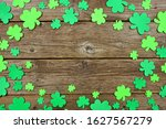 Small photo of St Patricks Day frame of shamrock decorations. Top view over an old rustic wood background. Copy space.