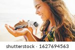 Small photo of Women with flapping hair hold wooden bowl with newborn turtle, close up portrait girl at the turtle sanctuary hatchery located on the beach.