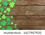 Small photo of St Patricks Day side border of shamrock decorations. Above view over an old rustic wood background. Copy space.