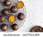 Small photo of Carrot energy balls (bliss balls), healthy sugar free candies covered by dark chocolate, decorated with chocolate shred. Top view. Vegetarian snack, food for health.