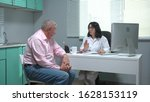 Small photo of Doctor explain something to old man in cabinet of hospital