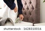 Man Hiding Dollar Banknotes...