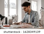 Small photo of Stylish and fashionable clothes designer man sews at a sewing machine. Sewing, design work, tailoring studio, tailor, designer clothes, manufactory, in the process of creative development