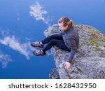 Woman Sitting On A Rocky Ledge...