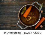 Small photo of Beef meat broth, ossobuco on bone, rich soup in saucepan, long slow languishing cooking. Healthy, nutritious broth, good for digestion. Dark wooden table, copy space