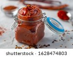 Traditional home made Korean red sause Gochujang can also be named Harissa Moroccan red hot chilli sause. Healthy spicy, vegetarian appetizer or snack with roasted red pepper dip, front view, close up