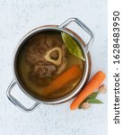Small photo of Paleo bone broth diet, beef meat soup. Low-carb food, keto recipe. Rich broth of slow languishing on beef and bones, prolonged boiling. Long cooking in pan