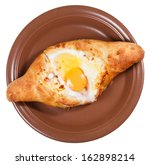 Small photo of top view of hachapuri by Adzharia (Georgian cheese pastry), filled with cheese and topped with a soft-boiled egg and butter on ceramic plate isolated on white background