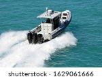 Police patrol boat powered by three outboard engines speeding on the Florida Intra-Coastal Waterway pff Miami Beach.