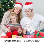 Stock photo family with tablet pc in front of christmas tree 162906500