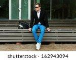 A Man Sitting Outside Wearing...