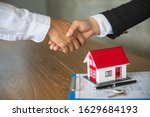 Small photo of Businessmen and investors in house trading.Holding hands to trust. Hand in hand to make a home purchase contract.Hand in hand with real estate brokers or agents.Is satisfactory Of the contract.