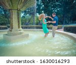 A couple dancing in a fountain in a park surrounded by greenery under sunlight