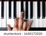 Small photo of right hand playing a C Major chord on the piano