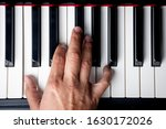 Small photo of right hand playing a A Minor inversion chord on the piano