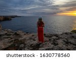Woman In Red Standing On Cliff...