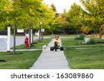 Stock photo young boy walking the dog with his tricycle on the nicely cut grasses in their neighborhood 163089860