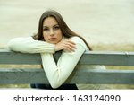 young lonely woman on bench in... | Shutterstock . vector #163124090