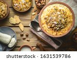 """Small photo of Arabic Cuisine; Traditional Egyptian dessert """"Om Ali"""" or """"Umm Ali"""" of soaked bread, milk and load of roasted nuts and raisins. Top view with close up."""