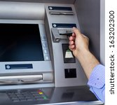 Small photo of Man's hand using the ATM