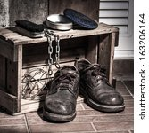 Rugged shoes in wooden box with cleaning set and chain, still light - stock photo