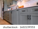 Small photo of Kitchen cabinets with white countertop black handles and tile backsplash