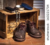 Rugged shoes in wooden box with cleaning set and chain, still life - stock photo