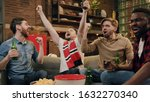 Small photo of Multiracial group of friends fanatic football fans watching soccer game on television celebrating goal raising hands jumping, screaming excited and ecstatic and crazy happy with beer bottles and pizza