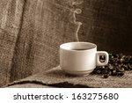 Coffee cup and white smoke on sack cloth. Dark background. - stock photo