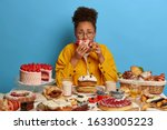 Small photo of Gluttony and overeating concept. Upset crying ethnic woman eats piece of cake reluctantly, sits at table with many desserts, isolated over blue wall, feels hungry and greedy, wears yellow jacket