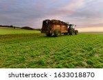 Small photo of farmer dispersing manure in fields