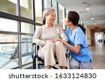 Small photo of friendly staff caregiver of nursing home talking to asian senior woman in hallway