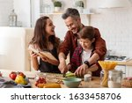Small photo of Happy family laughing loud. Mother, father and preschool son cooking on home kitchen. Mom holding cookbook. Dad helping child to chop celery for salad. Funny weekends. Communication and fun