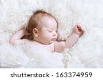 baby sleeping in soft fur bed... | Shutterstock . vector #163374959