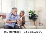 Small photo of Retirement couples take care of each other when they are sick, sitting on the couch in the house without the children to look after.