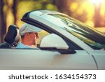 Young Retired Men Enjoying Summer Time Road Trip in His Convertible Car. Caucasian Men in His 30s Driving Cabrio Vehicle - stock photo