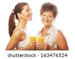 two women with orange juice. | Shutterstock . vector #163476524