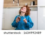 Small photo of young woman eating chocolate from a jar while sitting on the wooden kitchen floor. Cute ginger girl indulging cheeky face eating chocolate spread from jar using spoon savoring every mouthful