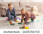 Small photo of Cheerful siblings playing twister game on floor having fun at home on weekend. Kids friendship and leisure activities.