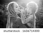 Small photo of Mother and daughter with braiding hair. Nice child girl with plaits. Hair in trendy weave plait