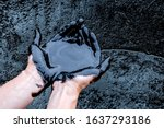 Small photo of rude oil surface background textured. Mineral oil in the hands of man. Caucasian hands cupped with black rock-oil