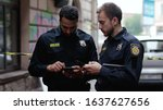 Small photo of Police at raid. Close-up two handsome policemen searching on smartphones tracking a criminal online. Friendly colleagues cops at police investigation area in the city street.