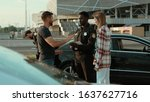 Small photo of People talking with the police in road accident area. Young offended woman argue with the driver after car crash. Focus on afro american baffled policeman near the car. Accident on the city road.