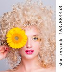 Small photo of Beautiful fashionable blonde girl with voluminous curly hairstyle, bare shoulders and a sunflower in her hands on a grey background. woman looking at camera and covering eye with a flower