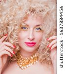 Small photo of Beautiful fashionable blonde girl in retro style with voluminous curly hairstyle, bare shoulders and a gold necklace looks at the camera and smiles.