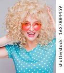 Small photo of Beautiful retro-style blonde girl with voluminous curly hairstyle, in a blue polka-dot blouse and pink glasses on a gray background